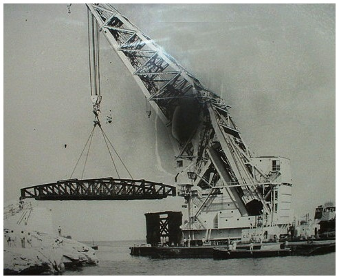 Floating crane lowering one of the bridge sections into place at the entrance to Grand Harbour ( St. Elmo's Viaduct ).